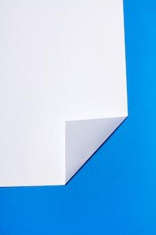 Pedaço de papel branco sobre um fundo azul.