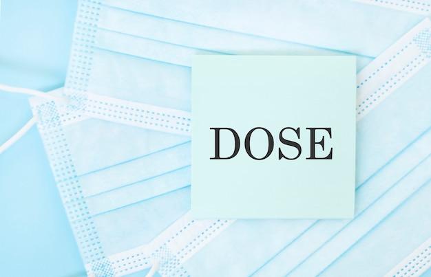 Pedaço de papel com a frase dose em uma pilha de máscaras médicas azuis