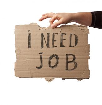 Pedaço de papel com a inscrição preciso de emprego