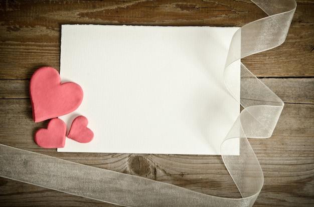 Pedaço de papel deitado com corações e fita em uma mesa de madeira