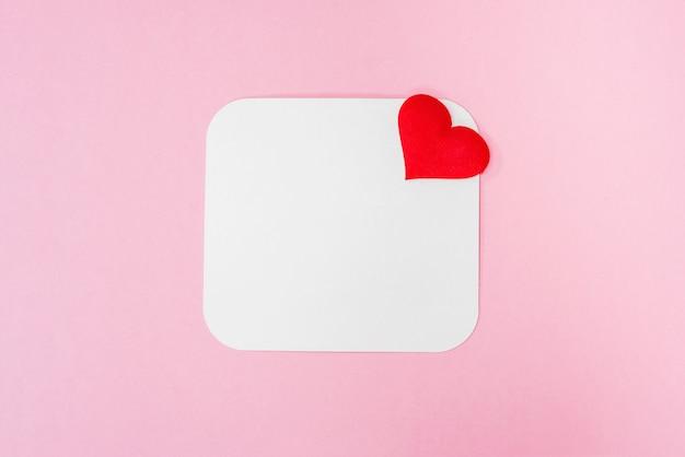 Pedaço de papel em branco e um coração vermelho em um fundo rosa, lugar para texto. cartão em branco, cartão postal