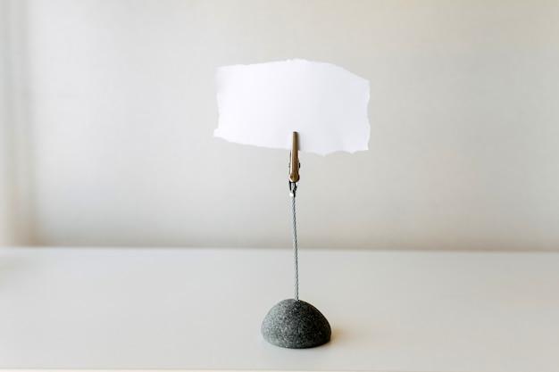 Pedaço de papel em branco para escrever notas em um suporte de metal.