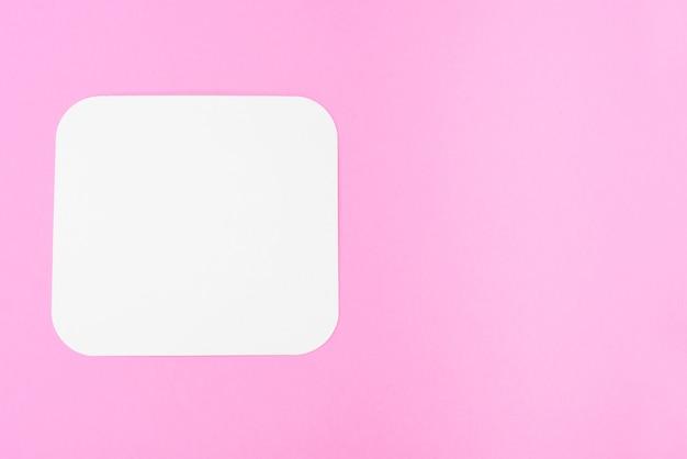 Pedaço de papel em branco sobre um fundo rosa, lugar para texto. cartão em branco