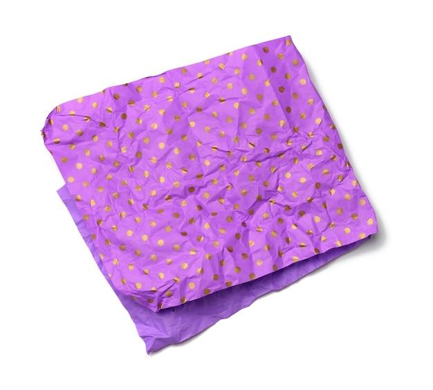 Pedaço de papel roxo amassado dobrado para embrulhar um presente isolado no fundo branco