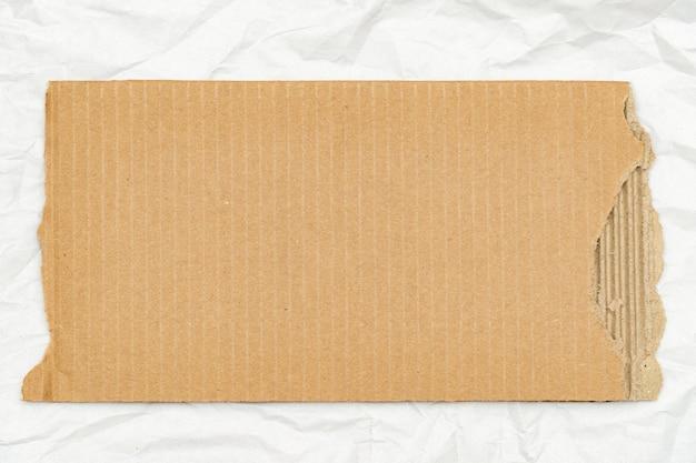 Pedaço de papelão rasgado em fundo de folha de papel com espaço de cópia