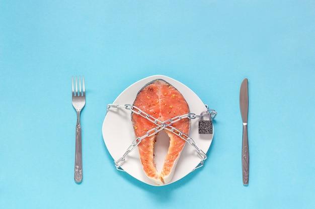 Pedaço de peixe vermelho no prato e corrente com cadeado fechado
