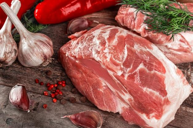 Pedaço de pescoço de porco cru na mesa de madeira. lombo de porco com especiarias e alecrim