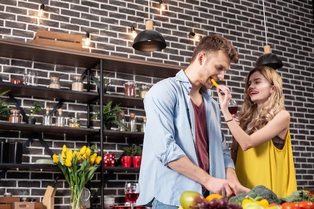Pedaço de pimenta. esposa carinhosa com cabelos loiros ondulados dando um pedaço de pimenta ao seu amoroso homem bonito