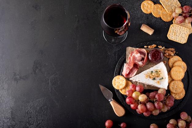 Pedaço de queijo brie com uvas, biscoitos e vinho tinto