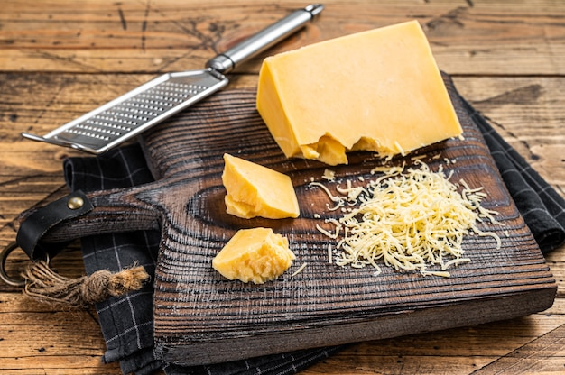 Pedaço de queijo cheddar ralado em uma placa de madeira. fundo de madeira. vista do topo.