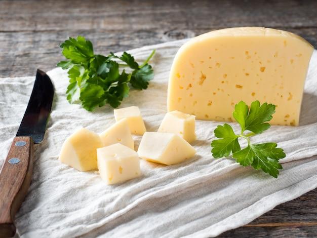 Pedaço de queijo com salsa em uma toalha de linho fundo de madeira rústico.