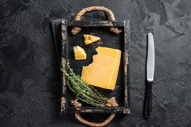 Pedaço de queijo duro suíço em tabuleiro de madeira. fundo preto. vista do topo.