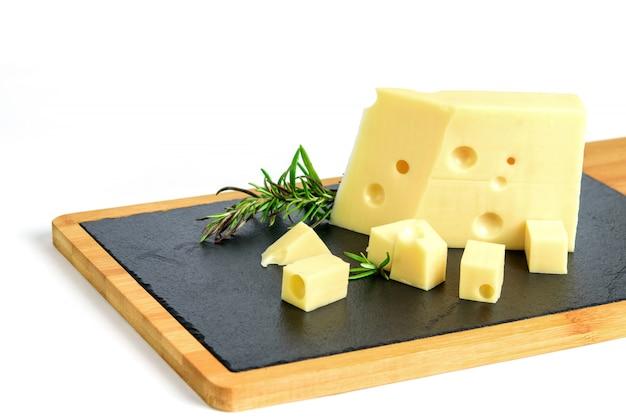 Pedaço de queijo emmental e alecrim no quadro de tapas preto.