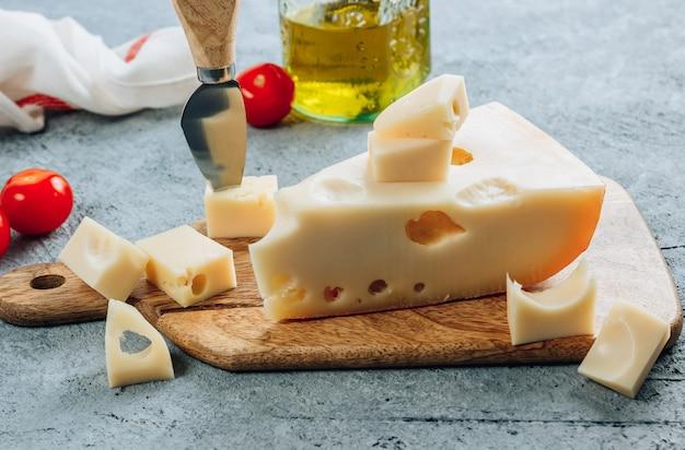 Pedaço de queijo maasdam de leite de vaca na tábua de madeira sobre bsckground de concreto.