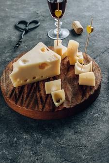 Pedaço de queijo maasdam de leite de vaca na tábua de madeira sobre o fundo de concreto.