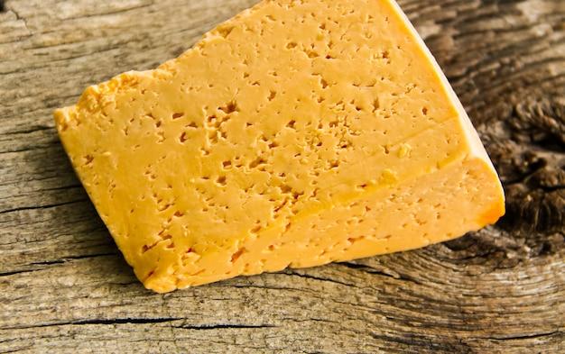 Pedaço de queijo no fundo de madeira