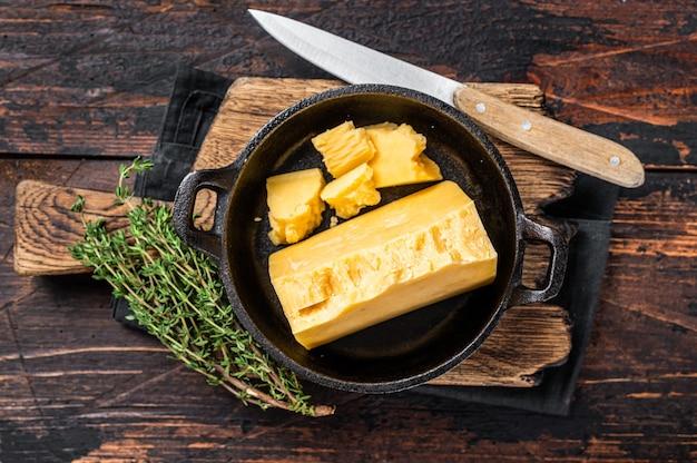 Pedaço de queijo parmesão duro em uma panela. fundo de madeira escuro. vista do topo.