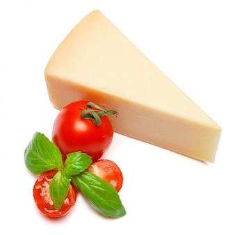 Pedaço de queijo parmesão e tomate na mesa branca