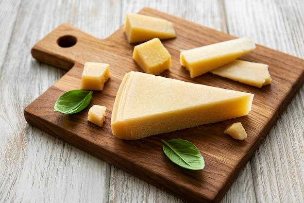 Pedaço de queijo parmesão em uma placa de madeira Foto Premium