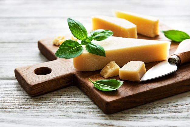 Pedaço de queijo parmesão em uma placa de madeira