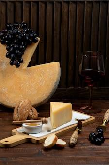 Pedaço de queijo parmesão servido com mel e uva