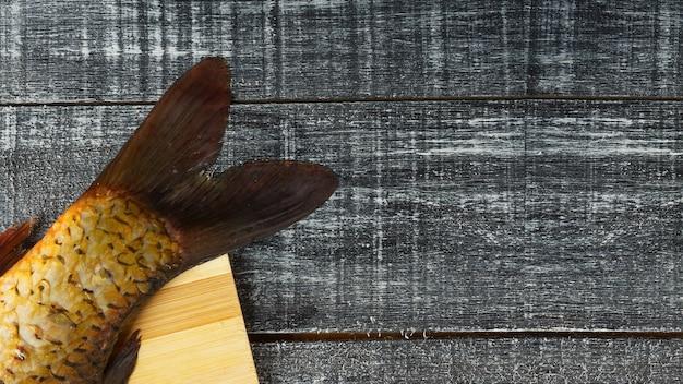 Pedaço de rabo de cavalo de carpa fresca contra um fundo preto com conceito de cozinha de espaço de cópia