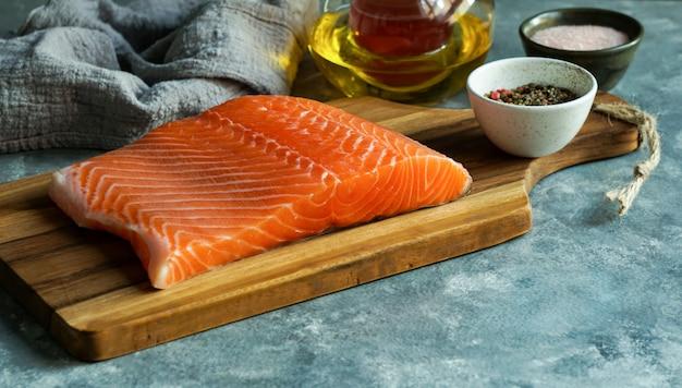 Pedaço de salmão fresco cru na tábua com óleo e ervas