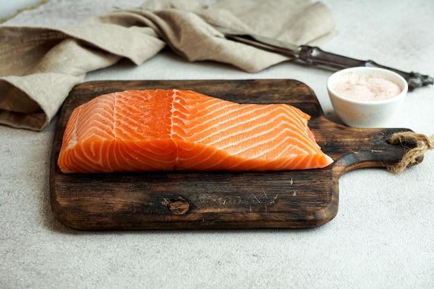 Pedaço de salmão fresco cru na tábua com sal