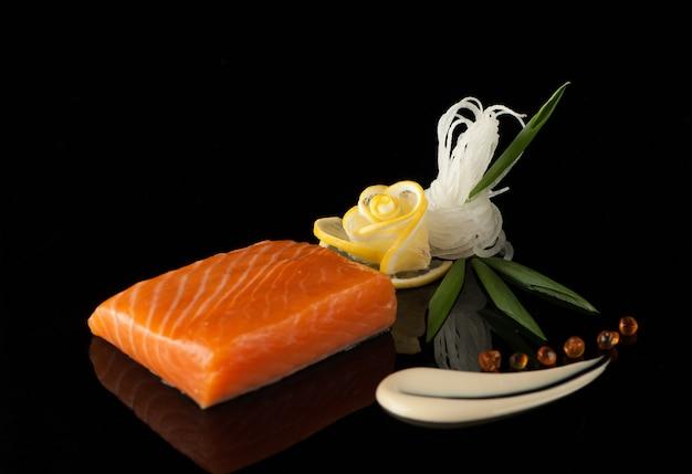Pedaço de sushi com limão e folha em um fundo escuro com reflexo
