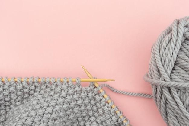 Pedaço de tecido de malha cinza em agulhas de madeira de bambu com novelo de lã, processo de tricô em fundo rosa.