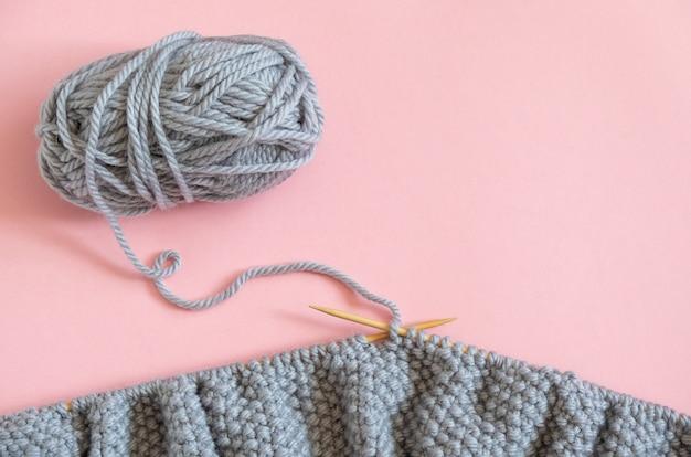 Pedaço de tecido de malha cinza sobre as agulhas com novelo de lã, processo de tricô em fundo rosa.