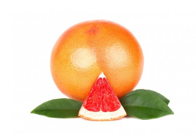 Pedaço de toranja, isolado no espaço em branco. fruta fresca. com traçado de recorte. toranja fresca com as folhas verdes isoladas.
