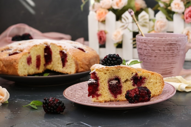 Pedaço de torta caseira com amoras e xícara de café na superfície escura. natureza morta