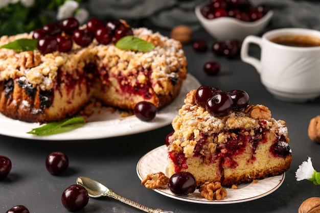 Pedaço de torta caseira de cereja com shtreisel e nozes em um prato branco sobre um concreto escuro