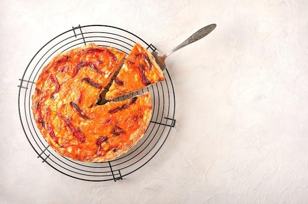 Pedaço de torta caseira de quiche com frango, tomate seco e queijo cheddar na omoplata