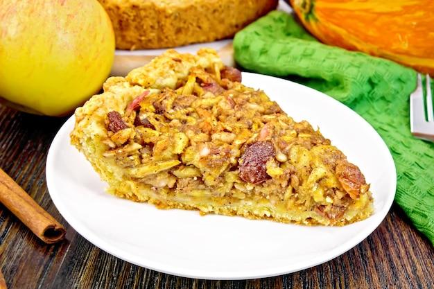 Pedaço de torta com maçãs, abóbora, passas e nozes em um prato branco, canela, guardanapo no fundo de uma placa de madeira escura