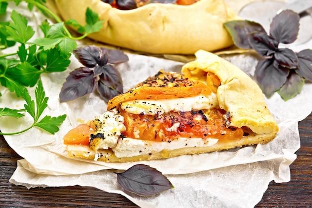 Pedaço de torta com tomate, requeijão e manjericão roxo em pergaminho no fundo da placa de madeira