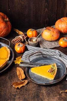 Pedaço de torta de abóbora caseira fresca de ação de graças, decorada com nozes e sementes na bandeja vintage na superfície de madeira rústica.