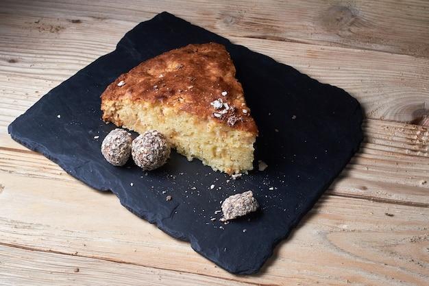 Pedaço de torta de maçã com chocolate ralado perto de bombons de trufas de chocolate. foco seletivo e pequena profundidade de campo.