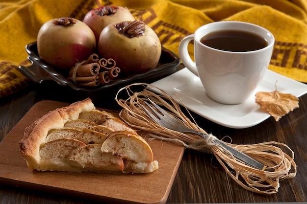 Pedaço de torta de maçã, maçãs assadas com canela e uma xícara de café preto