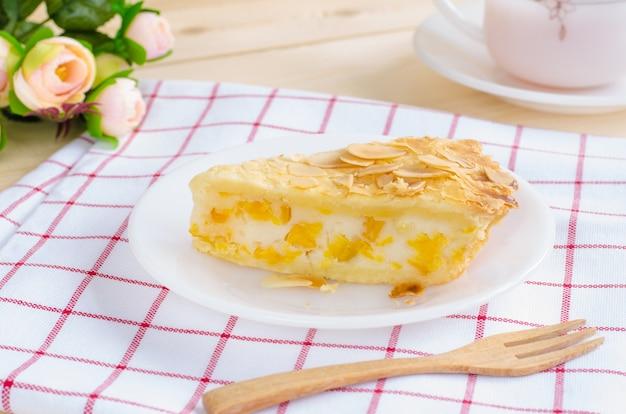 Pedaço de torta de milho delicioso na placa cerâmica branca sobre a mesa de madeira
