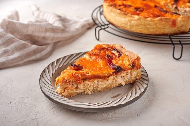 Pedaço de torta de quiche caseira com frango, tomate seco e queijo cheddar em prato de cerâmica