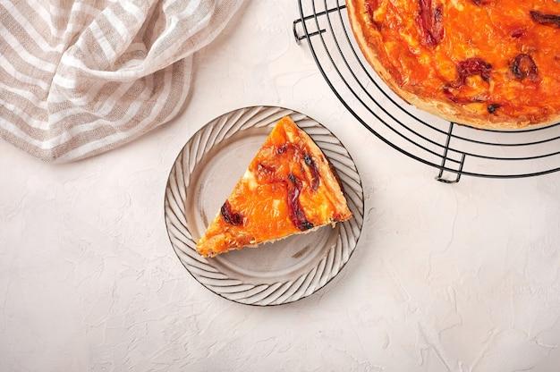 Pedaço de torta de quiche caseira com frango, tomate seco e queijo cheddar em um prato de cerâmica