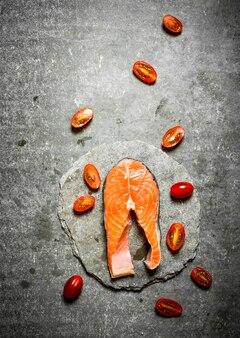Pedaço de truta crua e tomate na mesa cinza