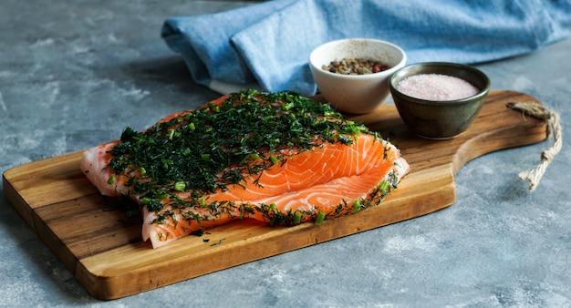 Pedaço fresco cru de salmão na tábua de corte