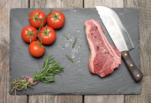 Pedaço fresco de carne crua de carne bovina, bife striploin numa superfície de madeira, vista superior. pedaço de carne marmoreado de nova york