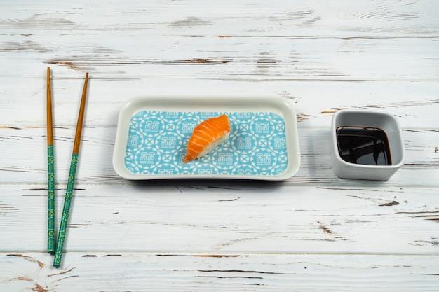 Pedaço fresco de sushi nigiri com pauzinhos de madeira