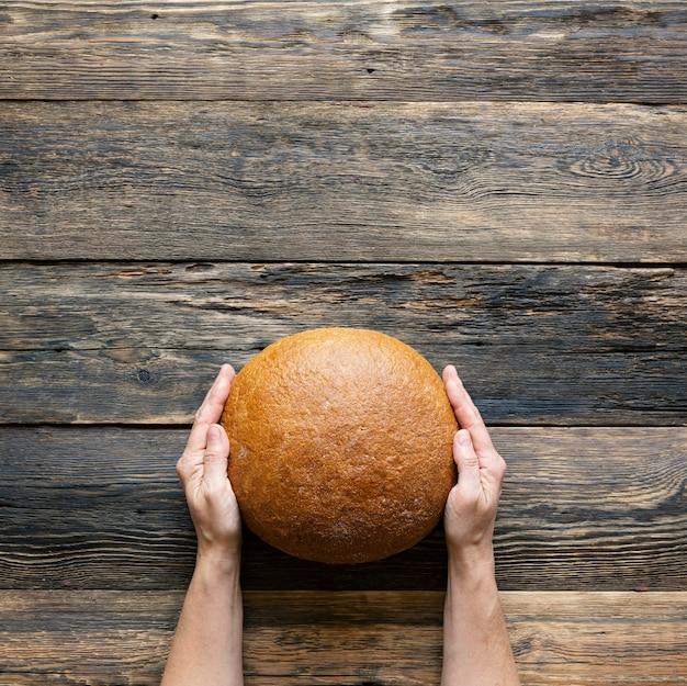 Pedaço redondo de pão cinza nas mãos de mulheres em fundo de madeira close-up