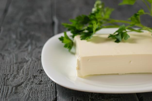 Pedaço retangular de queijo sérvio em uma tigela branca sobre uma mesa de madeira. vista de cima. produto lácteo. postura plana.