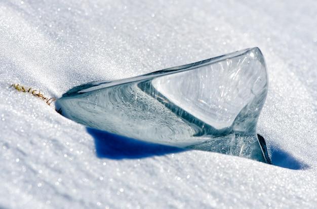 Pedaço transparente de gelo na neve perto do lago baikal
